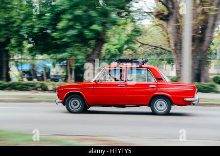 An old red Lada car in motion on a road in Havana, Cuba - Stock Photo