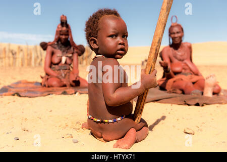 Young Himba boy child sits in front of two Himba women in a village in Northern Namibia. - Stock Photo
