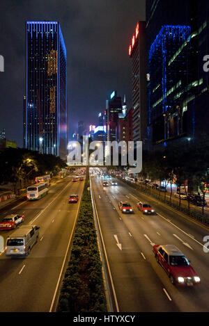 wide angle view busy design office. wide angle view of busy design office with workers at desks a skyscrapers and the traffic motion blur along gloucester road on hong kong