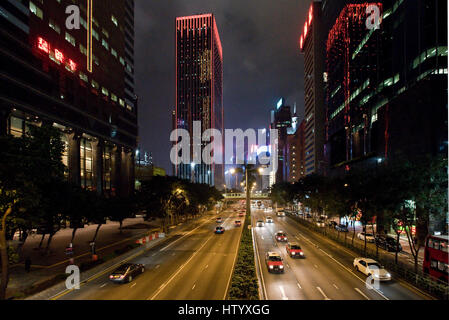 A view of skyscrapers and the traffic with motion blur along Gloucester Road on Hong Kong Island in the evening - Stock Photo