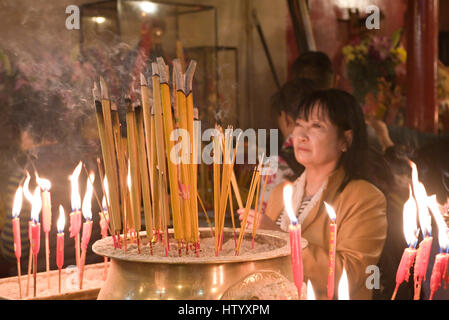 A local woman at the Man Mo Temple in Hong Kong lighting incense sticks prior to prayer.