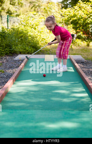 Young girl playing crazy mini miniature golf outdoors  Model Release: Yes.  Property Release: No. - Stock Photo