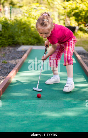Young girl playing crazy mini miniature golf outdoors - Stock Photo