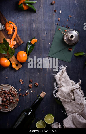 Citrus fruits, nuts and bottle of wine over blue wooden background. Top view. - Stock Photo