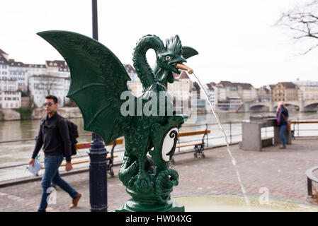Dragon water fountain on Basel river front with people, river Rhine and old town in the background. Basel old town, - Stock Photo