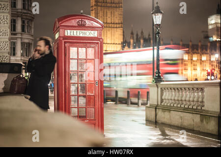 Man at the telephone near the red telephone box in London - UK - Stock Photo