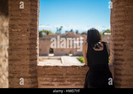 A girl enjoys the view looking out the window in Marrakesh in Morocco - Stock Photo