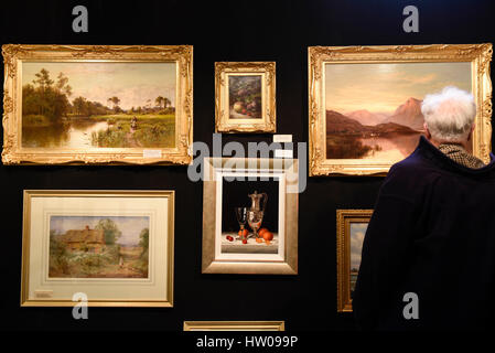 London, UK. 15th Mar, 2017. A visitor views paintings of display at The Chelsea Antiques Fair which opened at the - Stock Photo