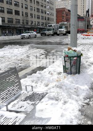 New York City, USA, 15 March, 2017. New Yorkers on the Upper Eastside intersection with metal bench and full garbage - Stock Photo
