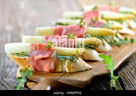 Delicious morsels with white asparagus on rocket leaves wrapped with Italian prosciutto - Stock Photo