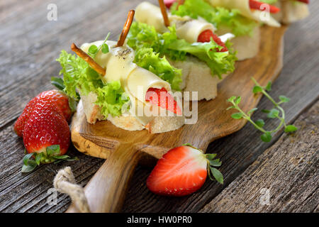 Canapes with delicious cheese rolls and strawberries on Italian ciabatta bread with lettuce leaves - Stock Photo