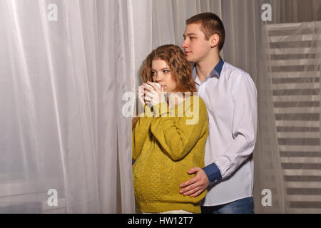 Husband embracing his pregnant wife. Pretty girl in sweater drinking a hot drink from a cup. Happiness and understanding - Stock Photo