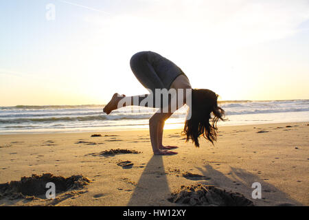 Beautiful woman doing yoga on the beach during sunset. - Stock Photo