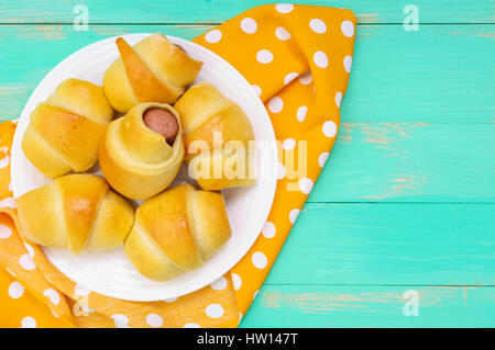 Freshly baked small buns on a white plate. Sausage in the dough. The top view - Stock Photo