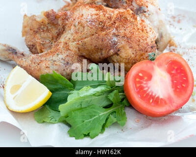 Whole roast grilled chicken with veggies on a paper - Stock Photo