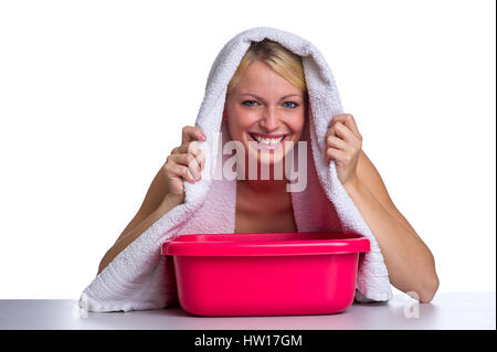 Blonde inhales about a bain-marie, Blondine inhaliert über einem Wasserbad - Stock Photo