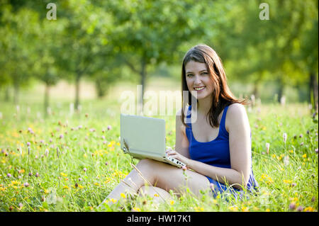 Young woman works with laptop, Junge Frau arbeitet mit Laptop - Stock Photo