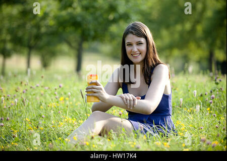 Young woman cremt to itself one, Junge Frau cremt sich ein - Stock Photo