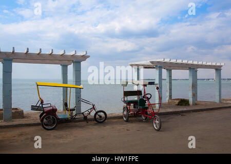 Typical bicitaxis are still in use and serve as transportation to locals and tourists. On the empty beach in Cienfuegoes - Stock Photo