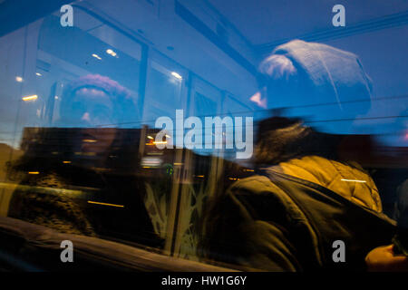 Two girls on a train looking out the window. Urban landscape in motion during the blue hour. - Stock Photo