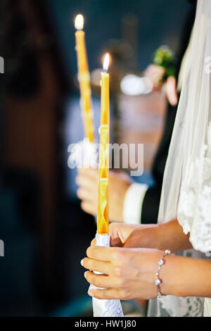 Bride and groom in church holding burning candles - Stock Photo