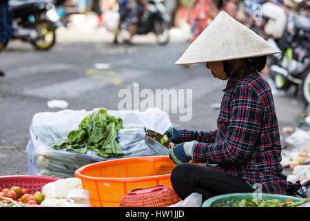 Ho Chi Minh, Vietnam. January 2017. A lady cutting vegetables at a street market. - Stock Photo