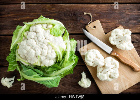 Fresh whole cauliflower on wooden rustic background, top view - Stock Photo