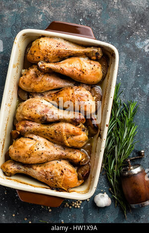 Grilled fried roast chicken legs, drumsticks on dark background, meat with ingredients for cooking, top view - Stock Photo