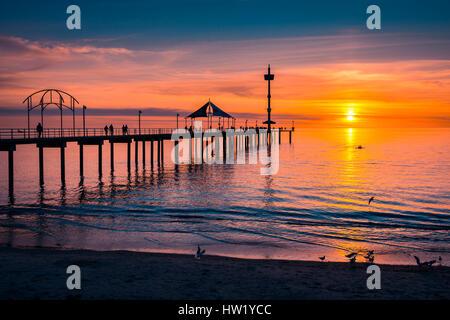 People walking on Brighton Jetty at sunset, South Australia - Stock Photo