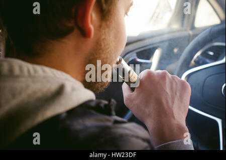 young vaper man with beard vaping mechanical mod. Guy smokes an electronic cigarette by blowing a smoke vapor. Bringing - Stock Photo