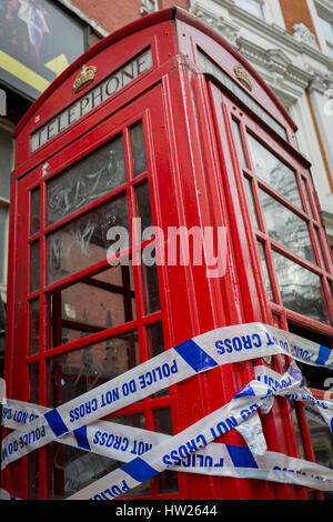 Police crime scene tape wrapped around a red phone box in Soho, on 8th March 2017, London borough of Westminster, - Stock Photo