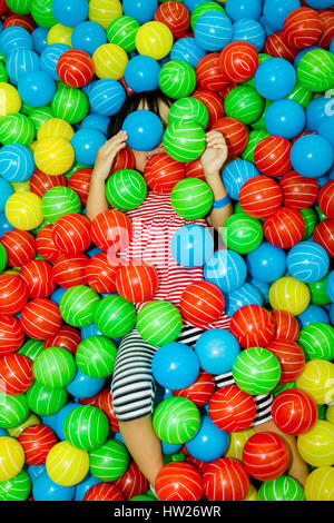 Asian Chinese girl hide in colorful ball pool at indoor playground. - Stock Photo