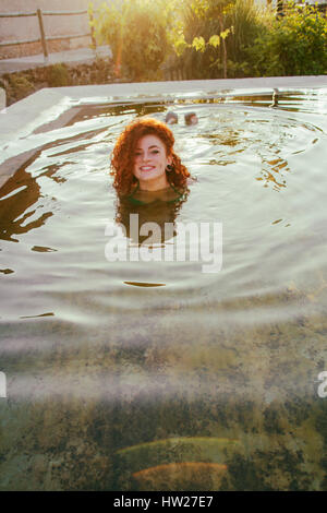 Young redhead woman enjoying a summer day in a natural pool - Stock Photo