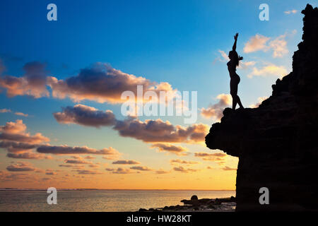 Black silhouette of happy young woman with slim body and hands up high in air on sunset sky background. Girl stand - Stock Photo