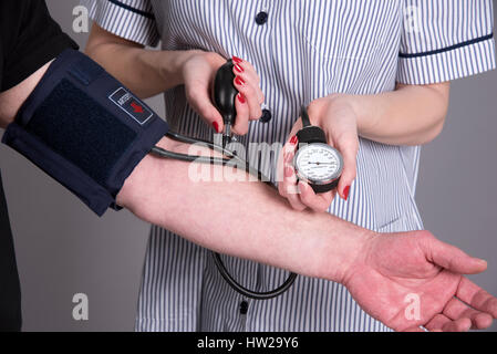 Nurse using a blood pressure monitor on a patient - Stock Photo