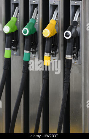 Nozzles on a fuel dispenser machine at a petrol station - Stock Photo