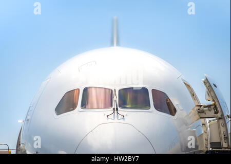 closeup of a passenger jet nosecone and cockpit with doors open - Stock Photo
