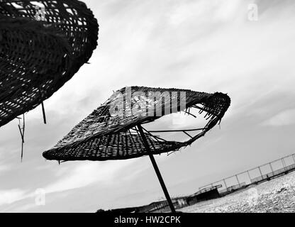 Black and white old sunshade with hole on deserted beach in sunny day - Stock Photo
