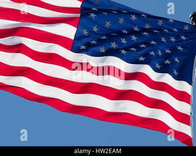 American flag waving in wind with blue sky background. - Stock Photo