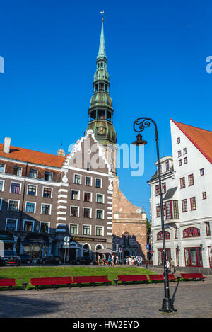Residential buildings on Albert Square on the Old Town of Riga, capital city of Republic of Latvia. Bell tower of - Stock Photo