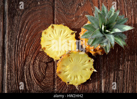 Fresh Asian small pineapple on wooden plate in outdoor hard sunlight and dark shadow - Stock Photo