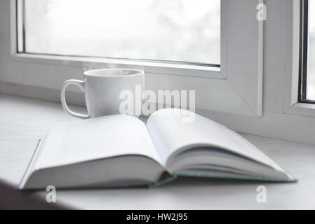 Cozy home still life: cup of hot coffee or tea and opened book on windowsill. Education concept, free copy space - Stock Photo