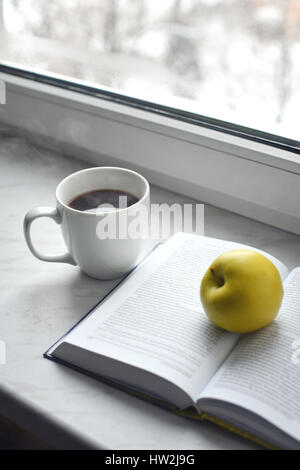 Cozy home still life: cup of hot coffee and opened book with green apple on windowsill. Free copy space - Stock Photo