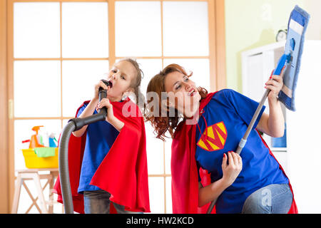 Preschooler girl and her mother dressed like superheroes. Middle-aged woman and kid playing while doing cleanup - Stock Photo