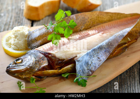 A smoked rainbow trout served on a wooden cutting board with horseradish, parsley, lemon  and baguette - Stock Photo