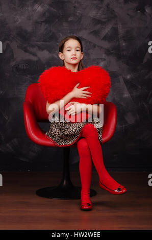 Pretty little girl wearing beautiful dress sitting in red armchair. She is holding plush heart in hands. Studio - Stock Photo