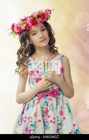Portrait of cute little girl in nice spring dress, with flower wreath on head, holds pink rose in hands - Stock Photo