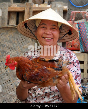 An elderly woman vendor offers a live chicken for sale in the markets of Hoi An in central Vietnam on April 16, - Stock Photo