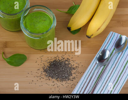 Green spinach, chia seed, banana and protein powder smoothie in two jars on the bamboo wooden surface. Healthy breakfast, - Stock Photo