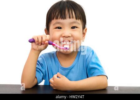 Chinese little girl brushing teeth in plain white isolated background. - Stock Photo